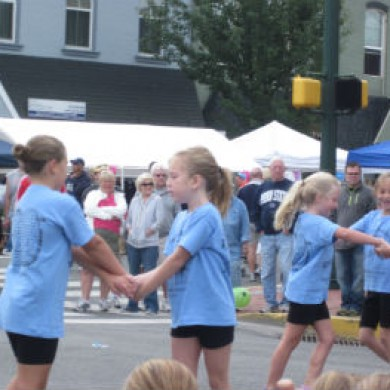 Young girls in blue shirts holding hands in street. downtown Selinsgrove, PA event