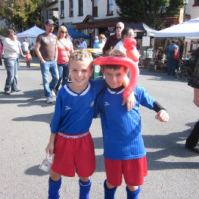 Two little boys in Selinsgrove soccer uniforms balloon animal on head fair downtown Selinsgrove, PA